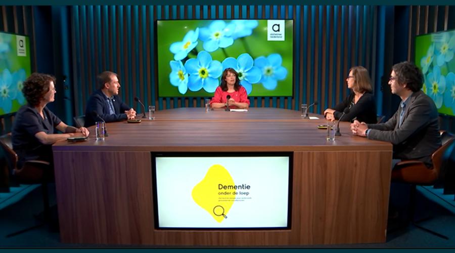 Vijf mensen zitten om een grote vergadertafel in een televisiestudio