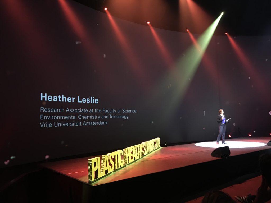 Een vrouwelijke wetenschappers geeft een presentatie op een groot podium
