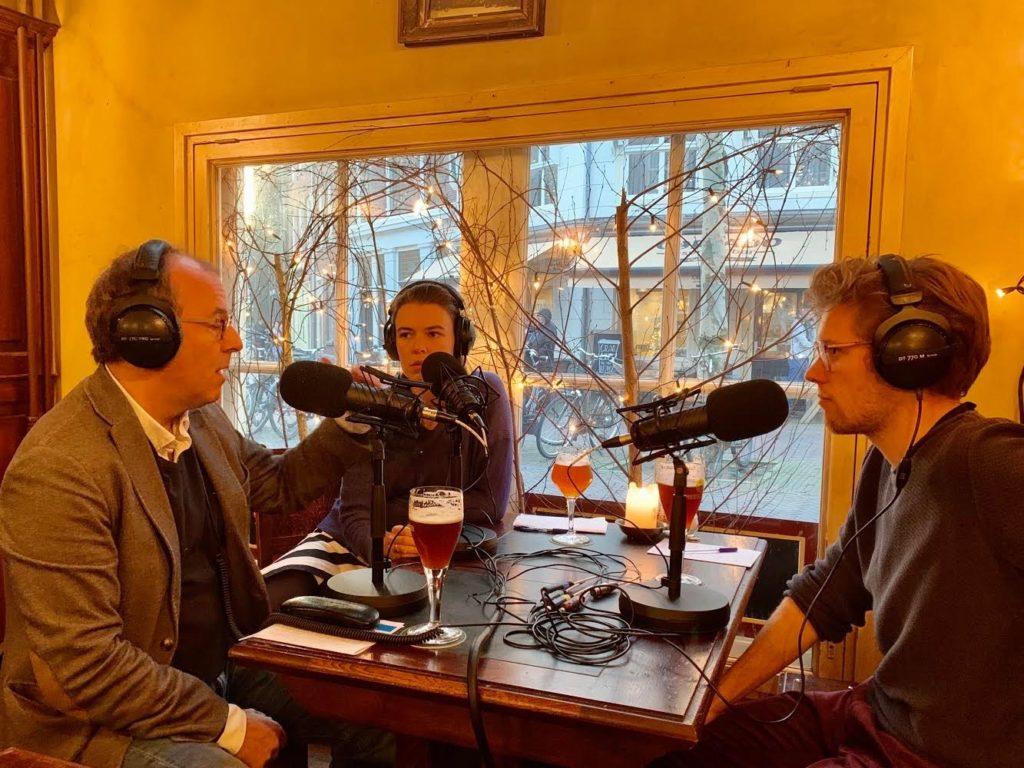 Drie wetenschappers zitten achter een microfoon