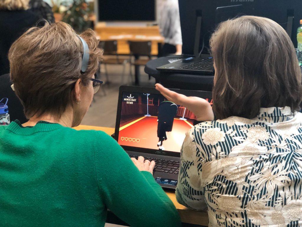 Foto van wetenschapper en deelnemer die samen een game spelen