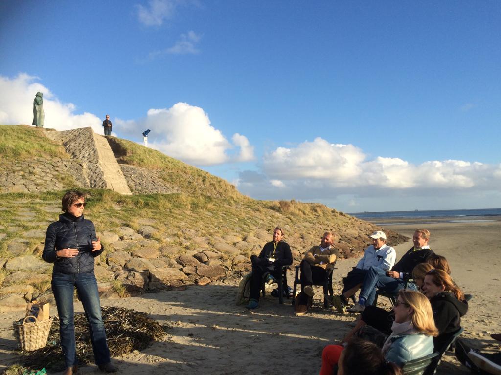 Een vrouw legt een groep mensen iets uit. Ze staan op de kust van een strand