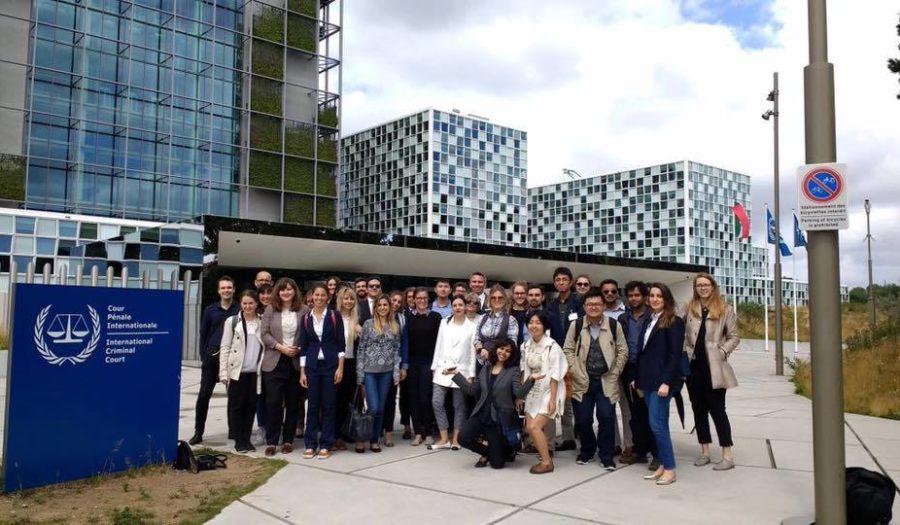 Een groep studenten staat voor het International Criminal Court-gebouw