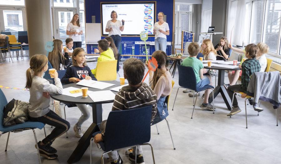 kinderen zitten in aan een tafel en stellen vragen aan een wetenschapper