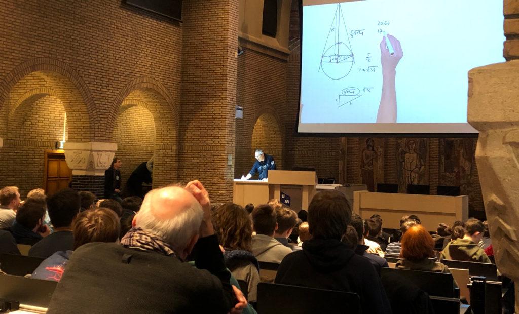 Foto van professor die wiskundige instructies geeft in een collgezaal