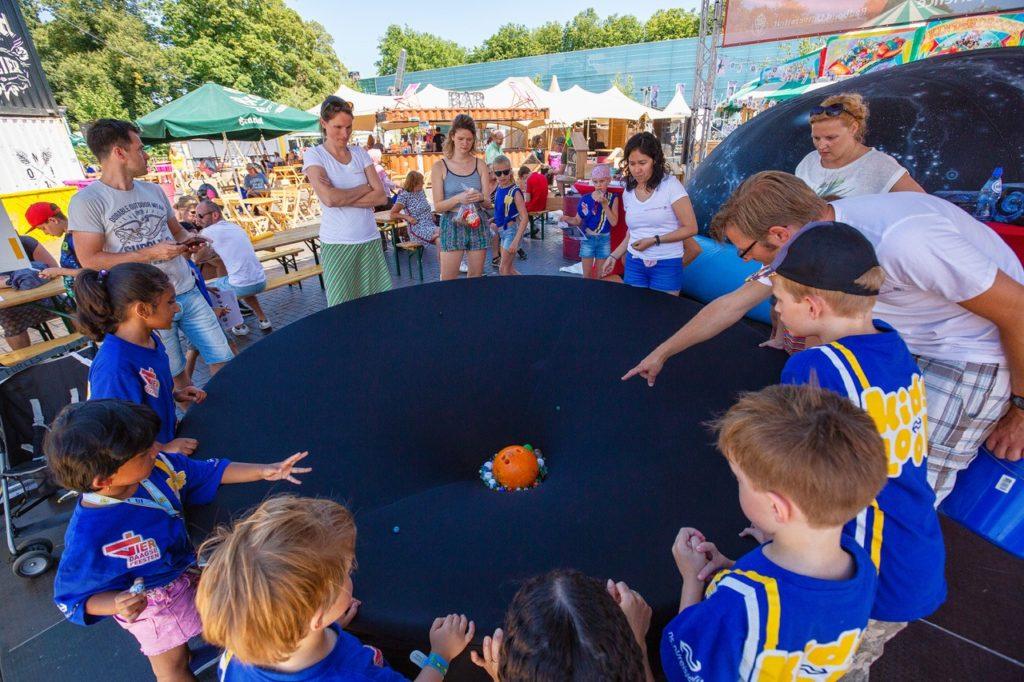 Wetenschapper educeert kinderen over planeten via grote bal op een tafel