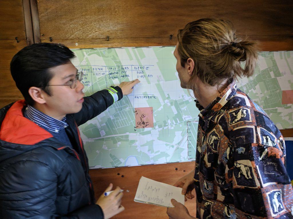 Een jongen wijst naar een kaart en legt iets uit aan een andere student