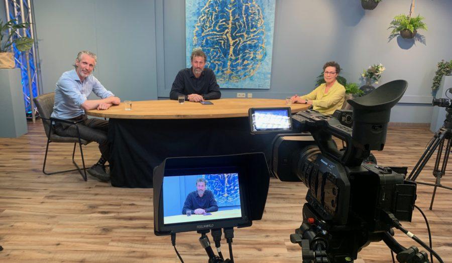 Drie presentators zitten aan de spreektafel waar ParkinsonTV wordt opgenomen
